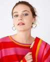 Detailed image of neckline and sleeve on pink and red striped sweater