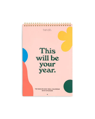 woman's hand writing on the wall calendar that's hanging on a bright yellow wall