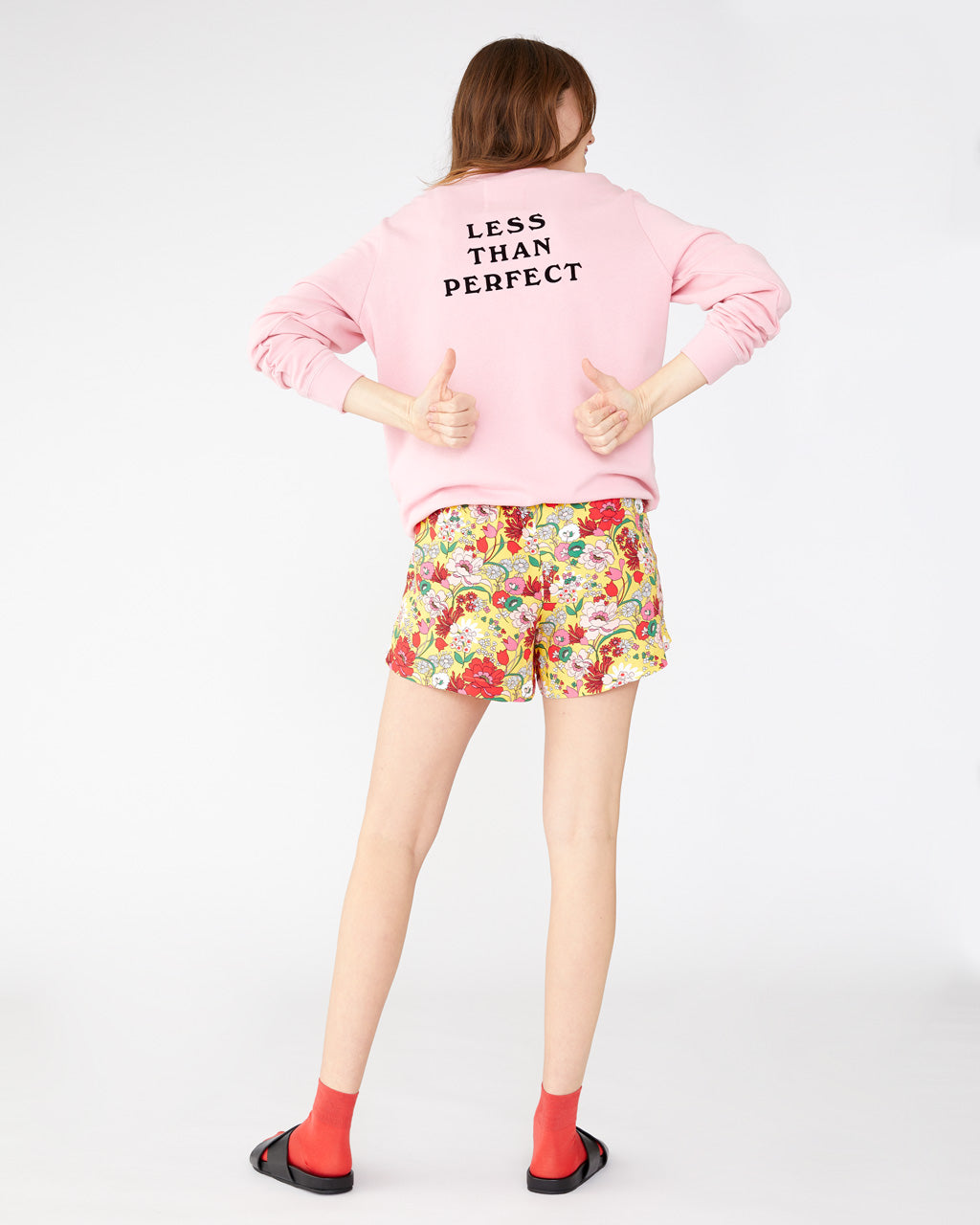Light pink long sleeve sweatshirt with the words less than perfect printed in black on the back