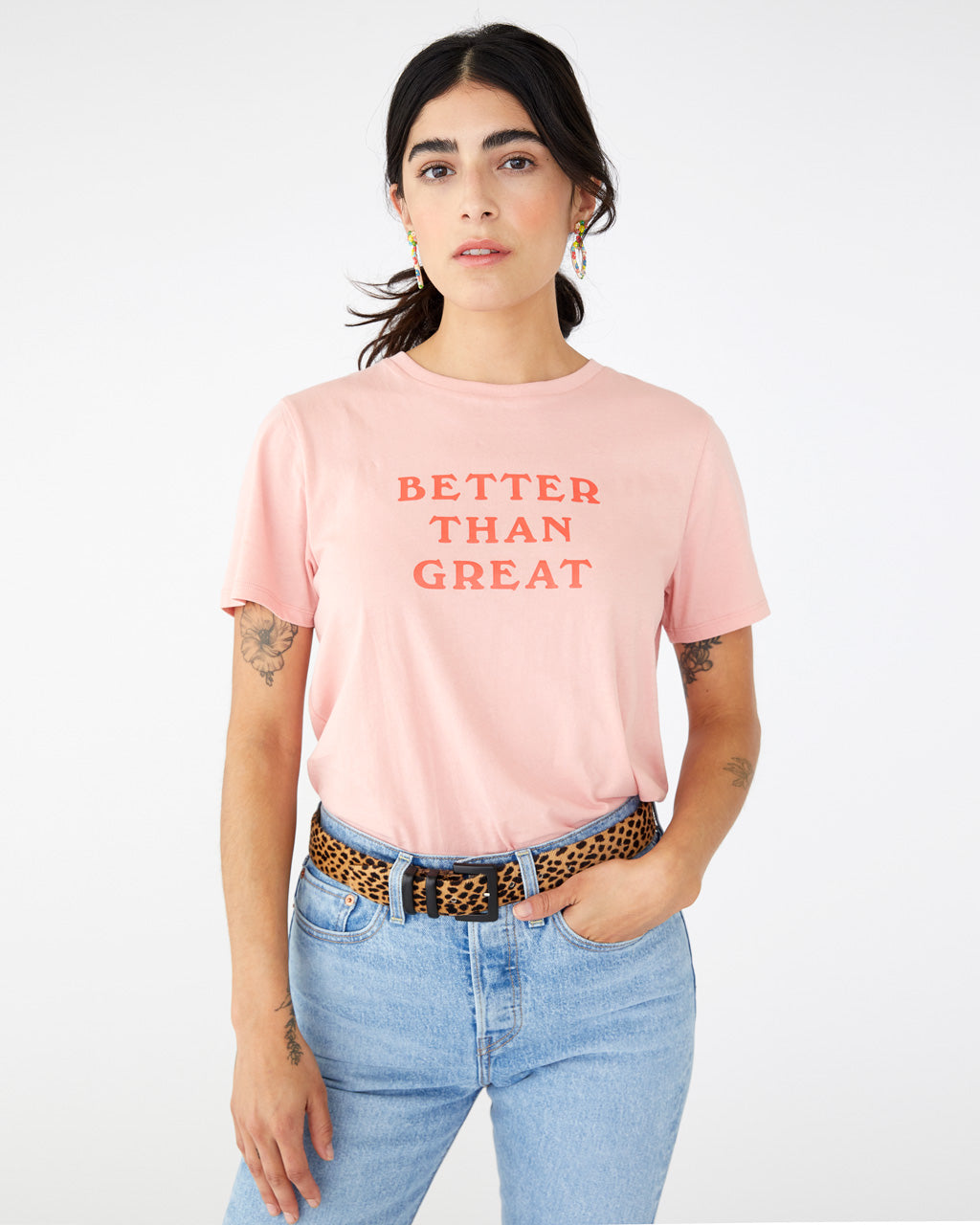 "Model wearing light pink crewneck tee with ""Better Than Great"" printed on the front center in darker pink text"