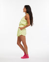model wearing our chill shorts in lime green stripe with matching tank and wearing hot pink socks