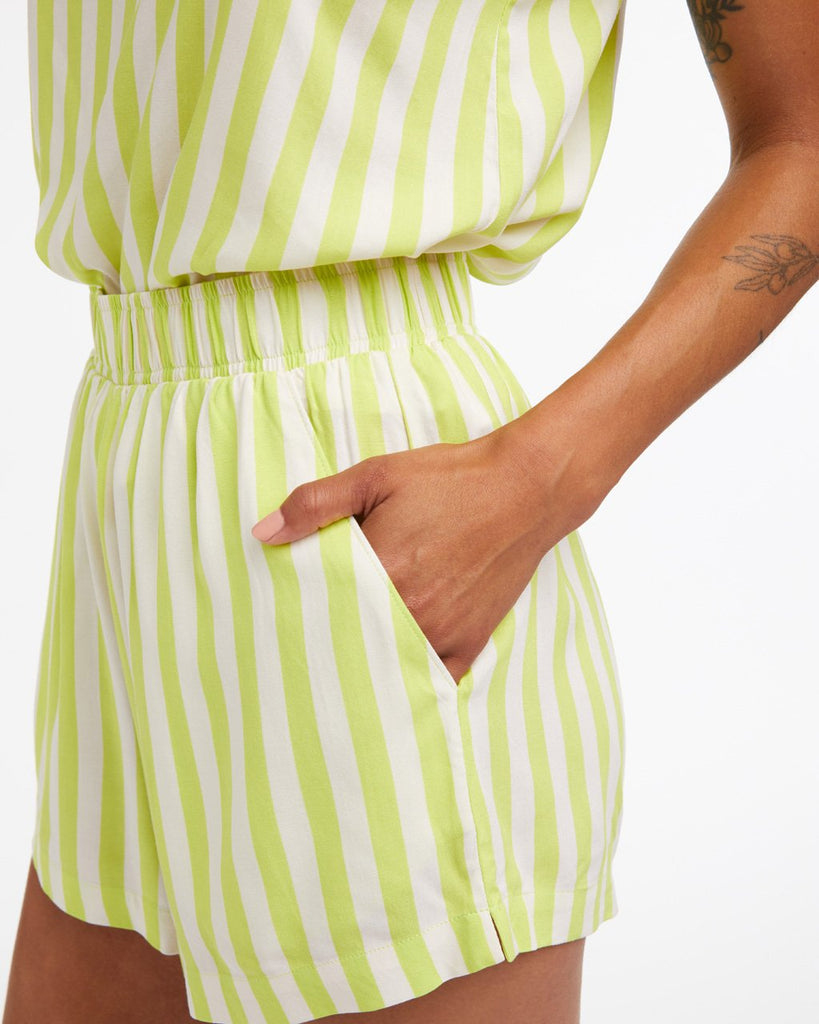 detailed image of model wearing our lime green stripe chill shorts with matching tank featuring side seam pockets