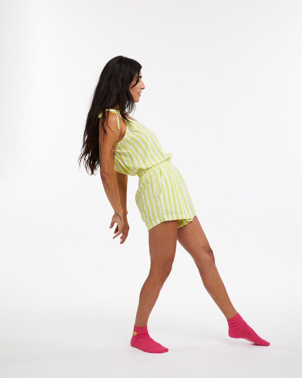 model leaned back wearing our lime green stripe chill shorts with matching tank and hot pink socks