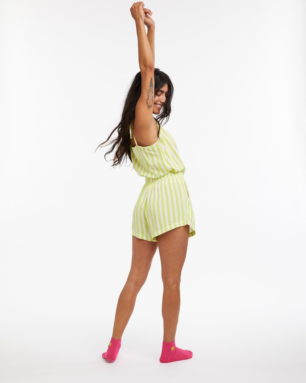 back view of model wearing lime green stripe breezy tank with matching shorts and hot pink socks