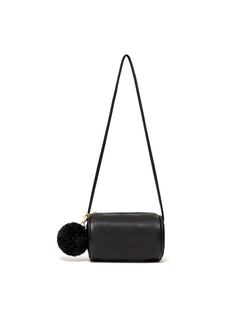 The onyx Buddy Cylinder Bag features a gold zipper and detachable pom-pom.