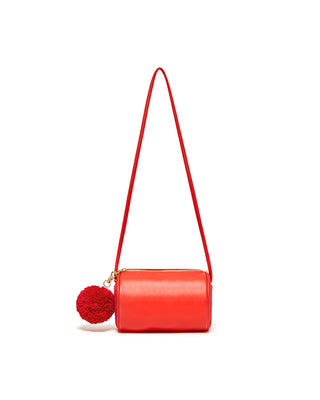 The punch Buddy Cylinder Bag features a gold zipper and detachable pom-pom.