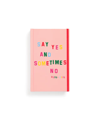 light pink classic planner with the words say yes and sometimes no on the cover in various colors