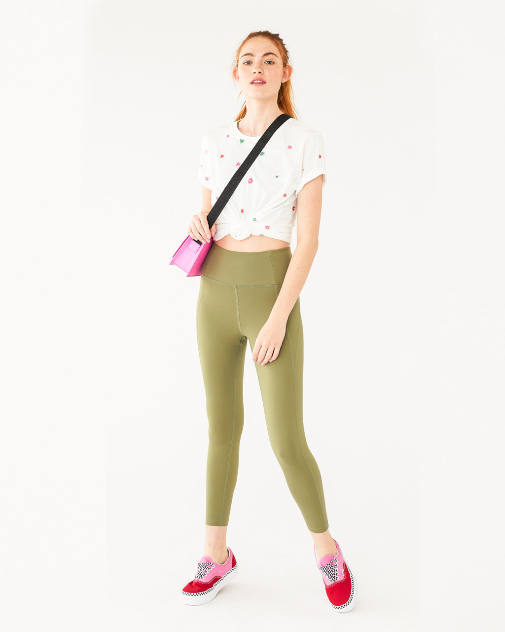 white cotton tee with a multi colored daisy pattern all over shown on model with olive colored leggings