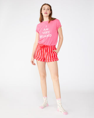 model shown wearing pink tee with the words i am very relaxed with red and pink striped shorts