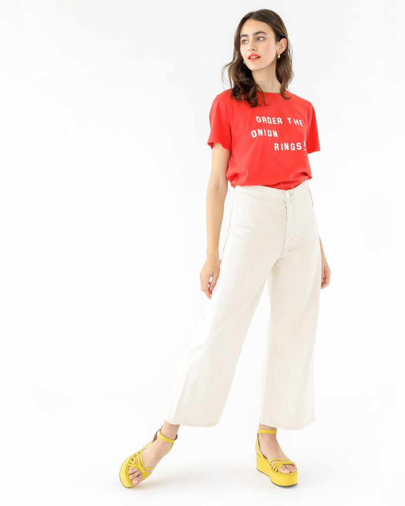 brunette model wearing red onion rings tee paired with off white wide leg pants