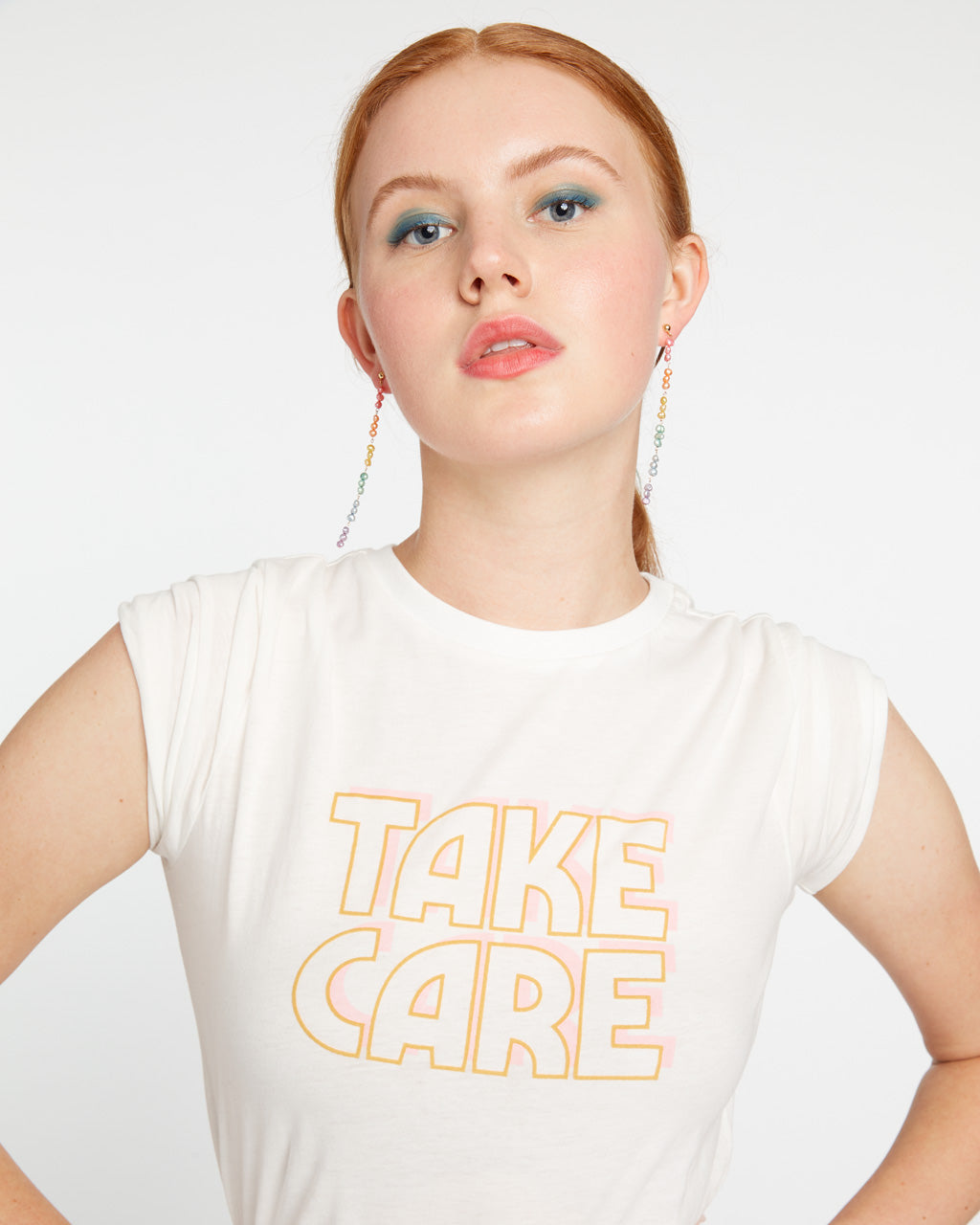 White short sleeve tshirt with yellow Take Care graphic.