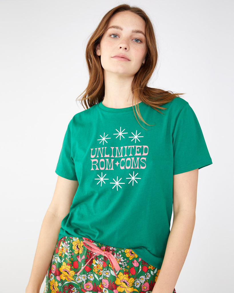 "woman wearing a dark green t-shirt with the words ""Unlimited Rom Coms"" in pink uppercase text"