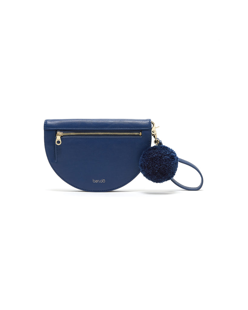Features an exterior zipper pocket and removable wristlet keychain with synthetic wool pom pom.