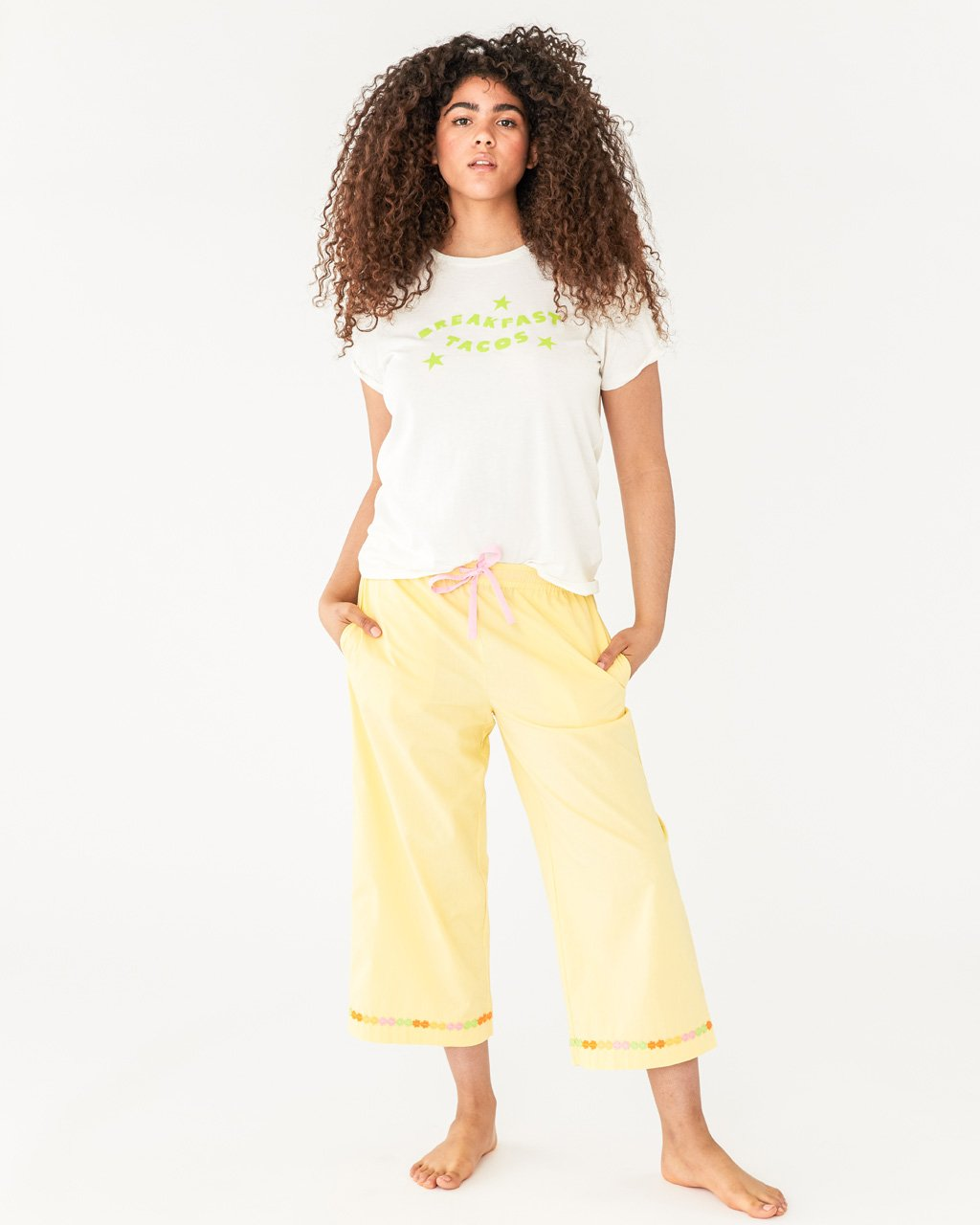 model wearing yellow cropped leisure pants with a daisy chain feature on the bottom of the leg, paired with breakfast tacos tee