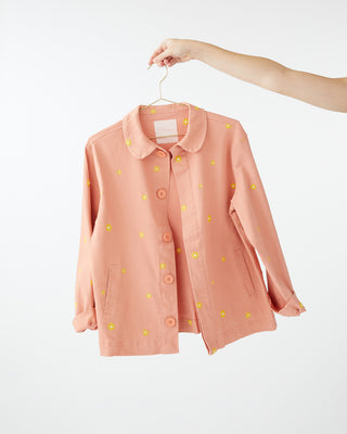 salmon colored work jacket with a yellow daisy pattern all over