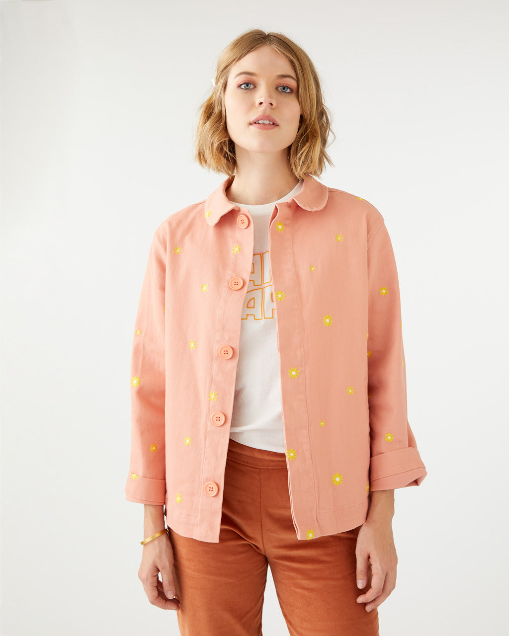salmon colored work jacket with a yellow daisy pattern all over shown on model with a white graphic tee and rust colored pants