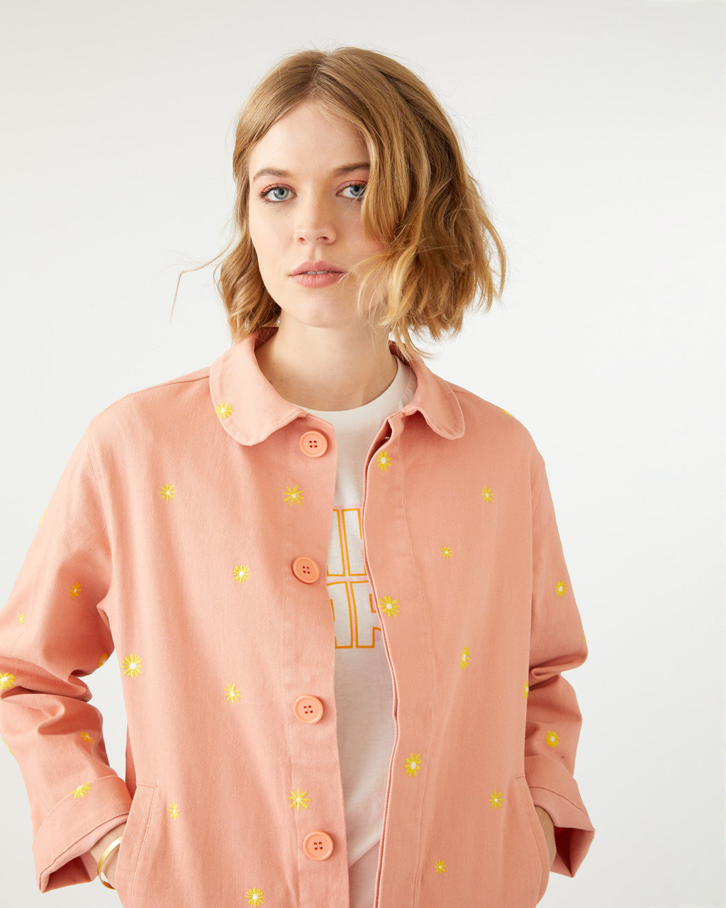 salmon colored work jacket with a yellow daisy pattern all over shown on model
