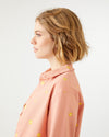 salmon colored work jacket with yellow daisy pattern all over and a boxy fit