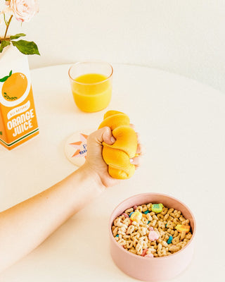 model's hand squeezing a croissant de-stress ball beside a bowl of cereal and a glass of orange juice