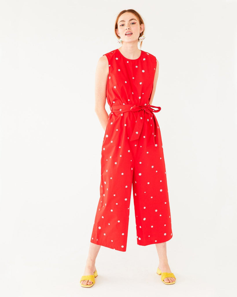 red tank jumpsuit with white daisy pattern all over shown on model