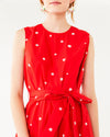 close up of model wearing red jumpsuit with daisy pattern all over featuring tie belt