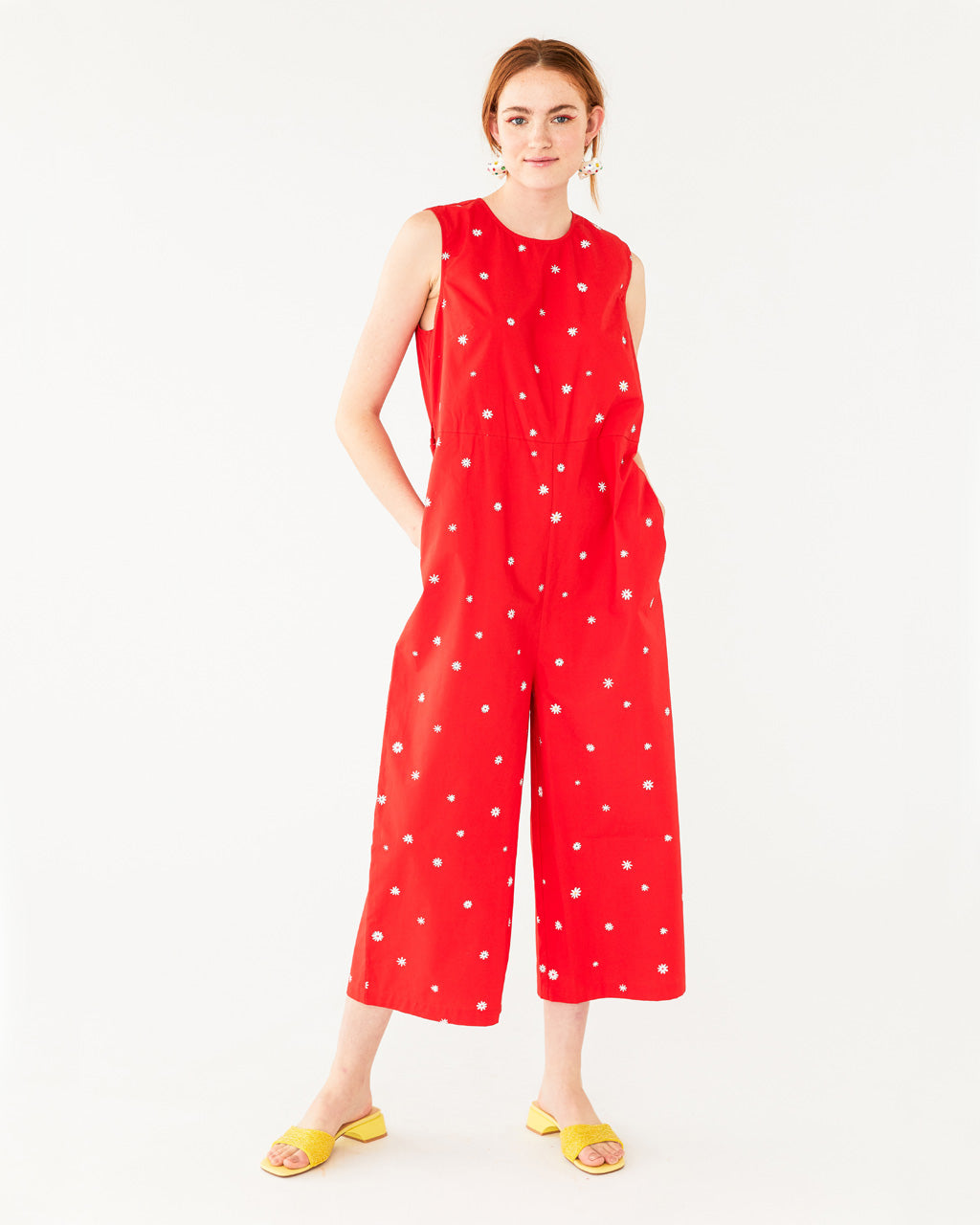model wearing red jumpsuit with a white daisy pattern all over with out using tie belt
