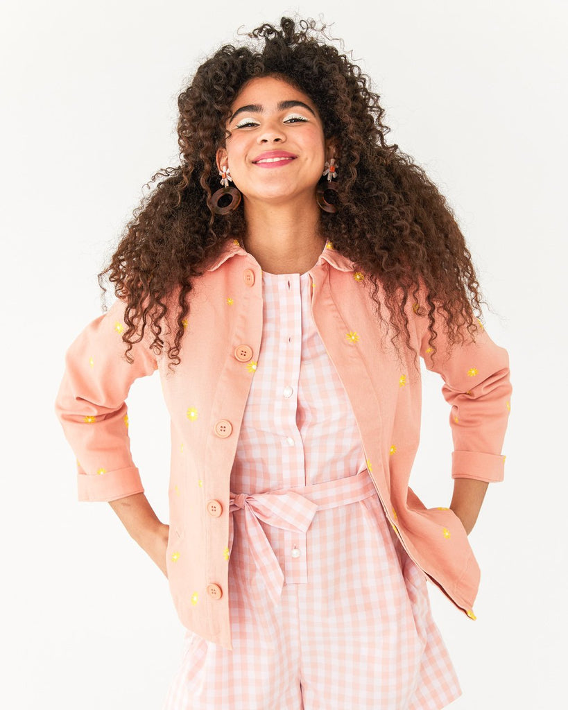 model wearing white and pink picnic plaid romper paired with daisy work jacket