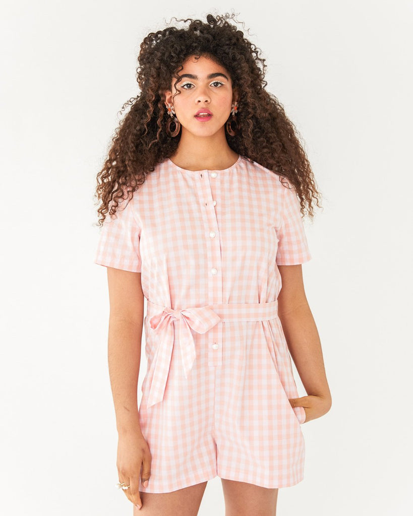 model wearing pink and white picnic plaid romper with tie belt and button-up front