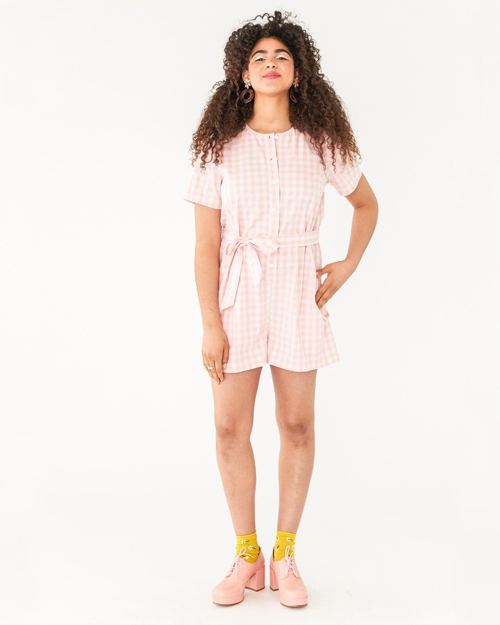 model wearing pink and white picnic plaid romper with tie belt and button-up front paired with pink heeled shoes and yellow socks