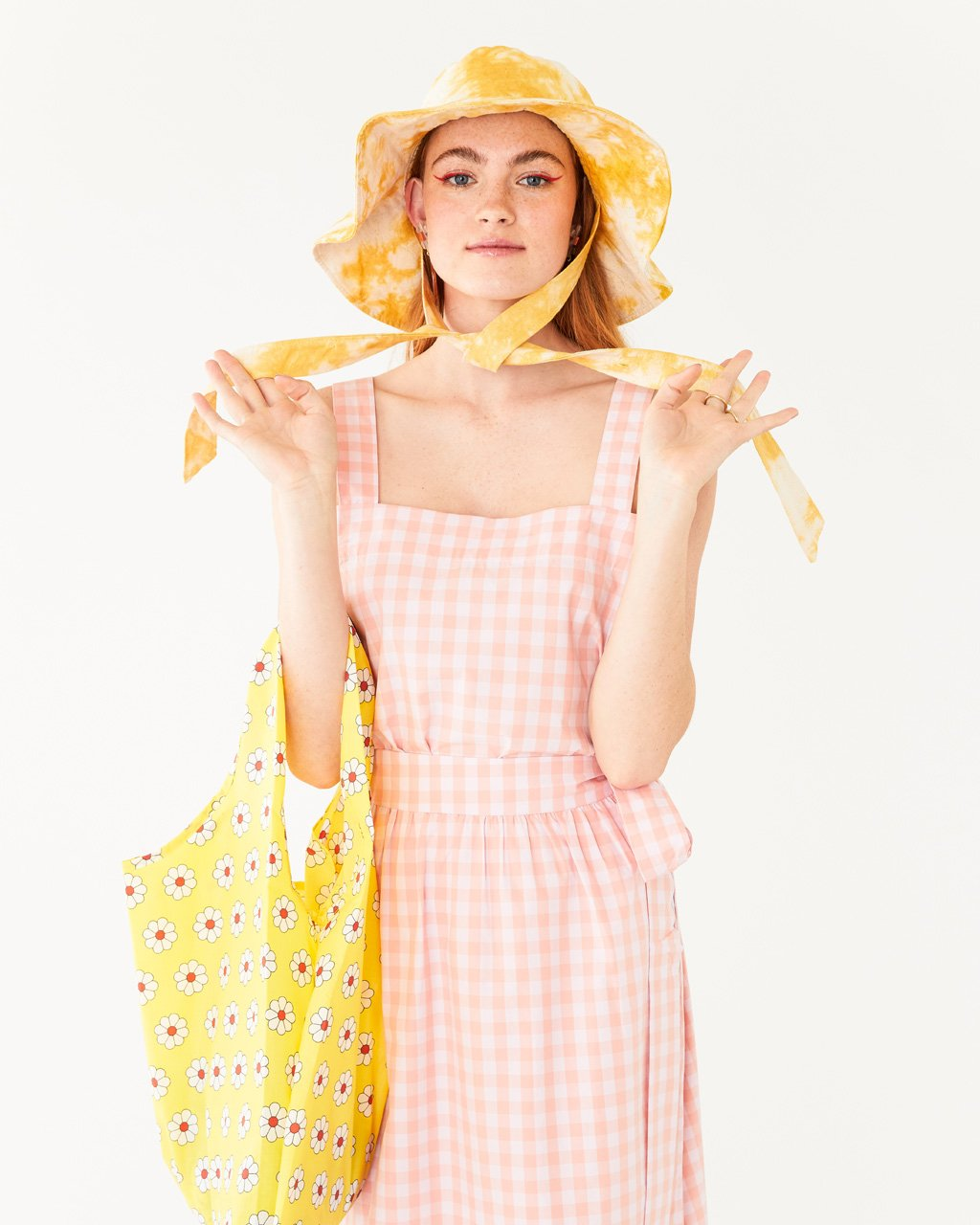 model wearing white and pink plaid tank paired with matching skirt and yellow tie dye hat and daisy baggu