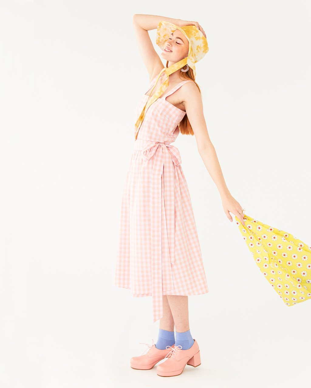 model wearing pink and white picnic plaid skirt with matching tank, pink heeled shoes, yellow tie dye hat, and carrying a yellow daisy baggu