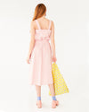 back view of model wearing pink and white picnic plaid skirt with matching tank top and carrying a yellow daisy baggu