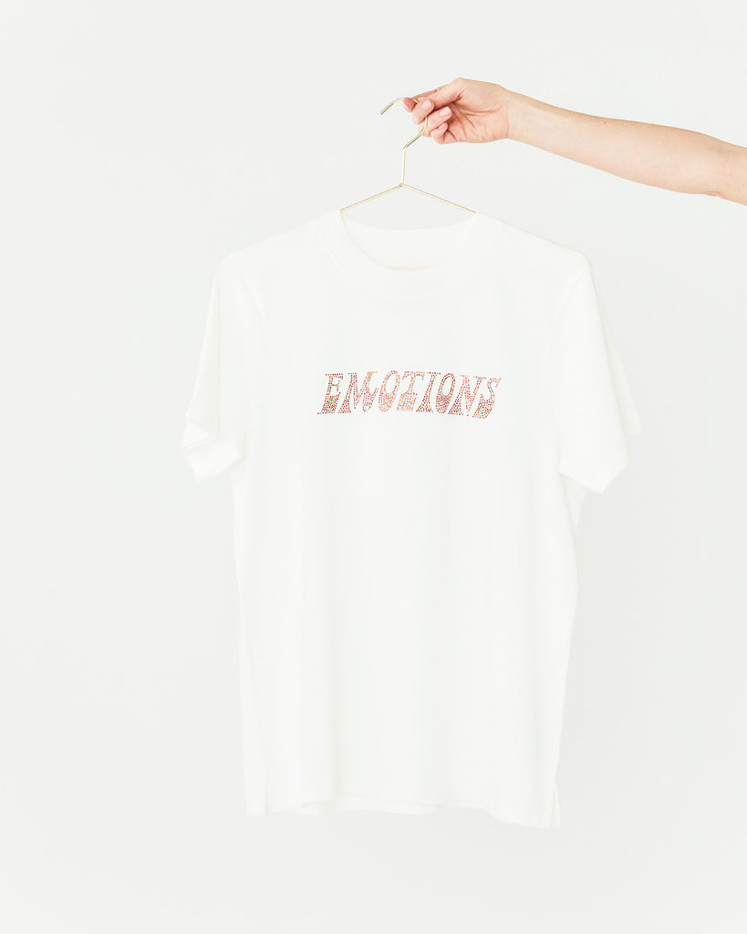 solid white tee with the word emotions placed on the front in rhinestones