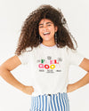 model wearing white feel good tee with a pastel purple collar and paired with blue and white stripe pants