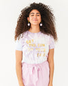 model wearing pastel tie dye shirt with the words get the sun on your face paired with a pink skirt