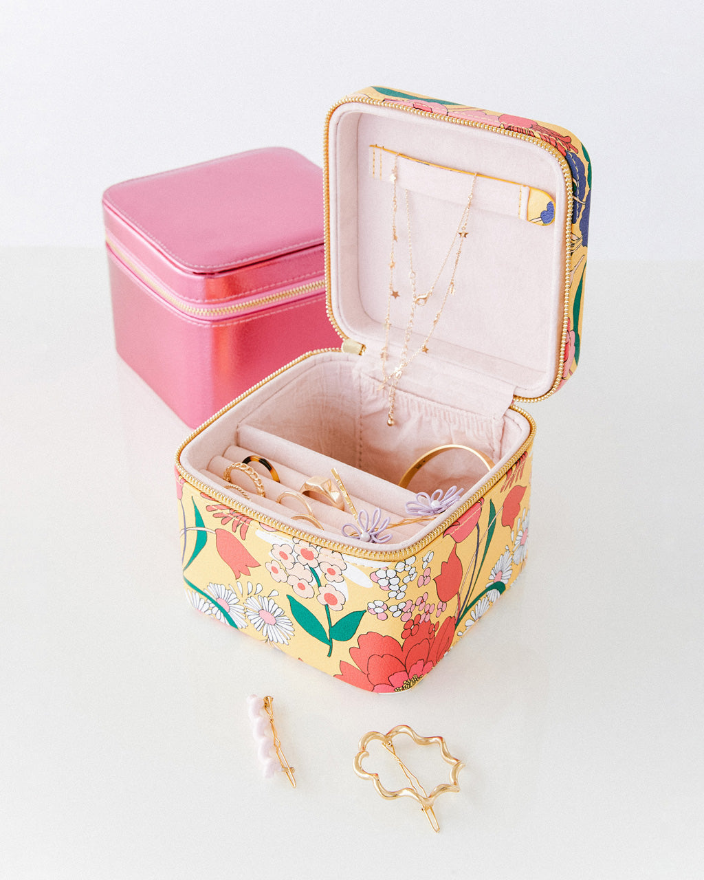 two zipper jewelry boxes shown with jewelry and hair accessories