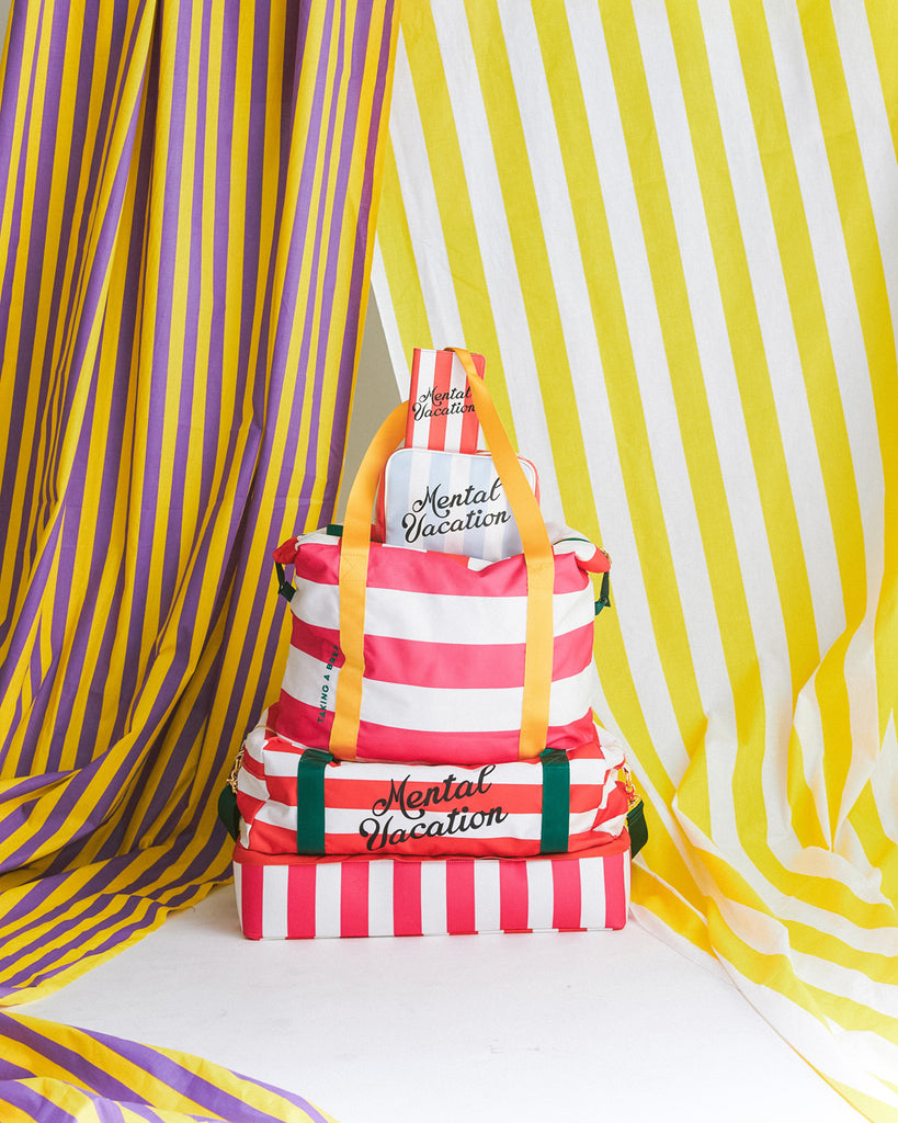 getaway weekender bag in swim club stripe shown sitting on top of the traveler bag and featuring mental vacation toiletry bag and mental vacation passport holder