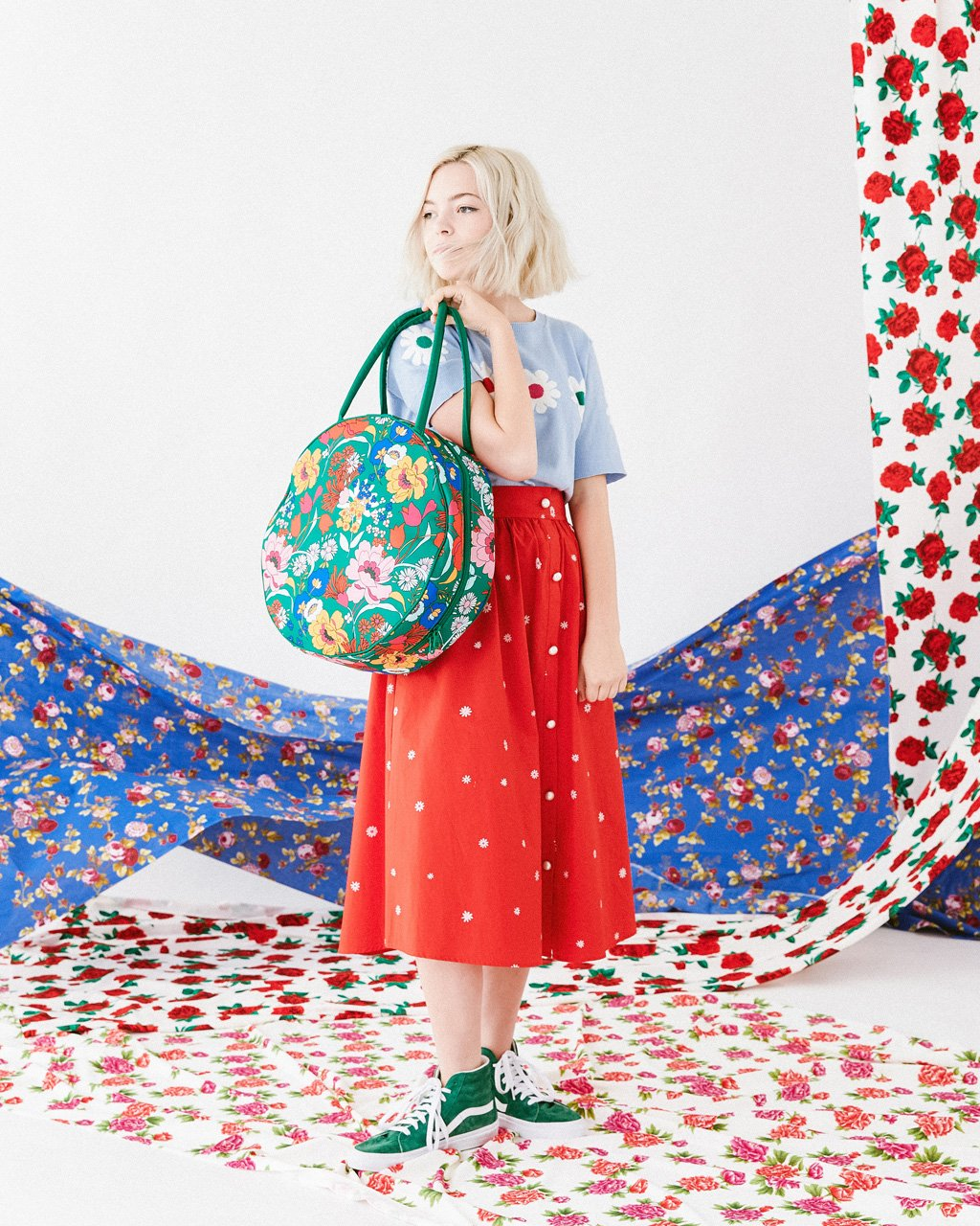 model wearing nutmeg daisy skirt with short sleeve daisy sweater holding emerald super bloom cooler bag