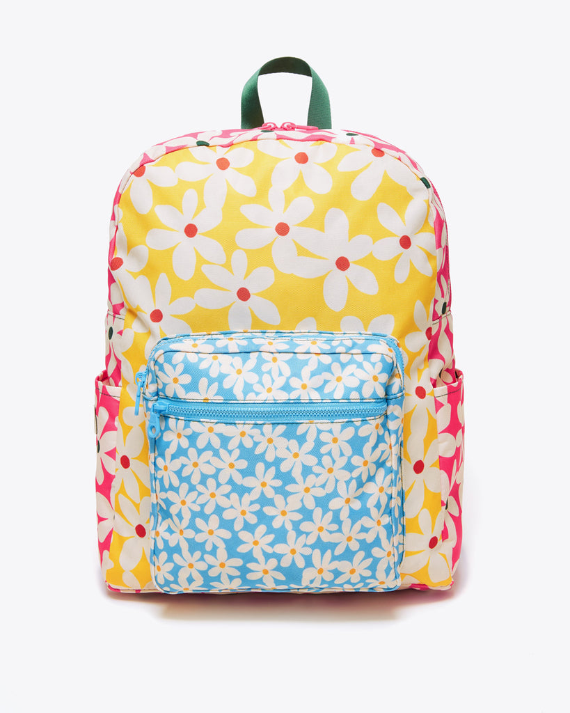 canvas backpack featuring a front packet and two side pockets, printed with a color block daisy pattern