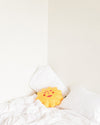 Sun shaped throw pillow shown on bed