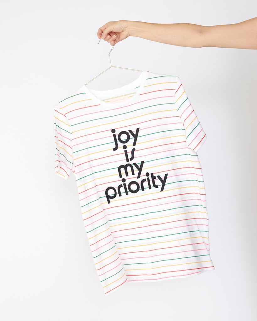 Colorful striped jersey shirt with the words joy is my priority shown on hanger