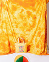 cooler bag with the words make time for sunshine shown in front of a yellow tie dye back drop and our sunburst beach ball