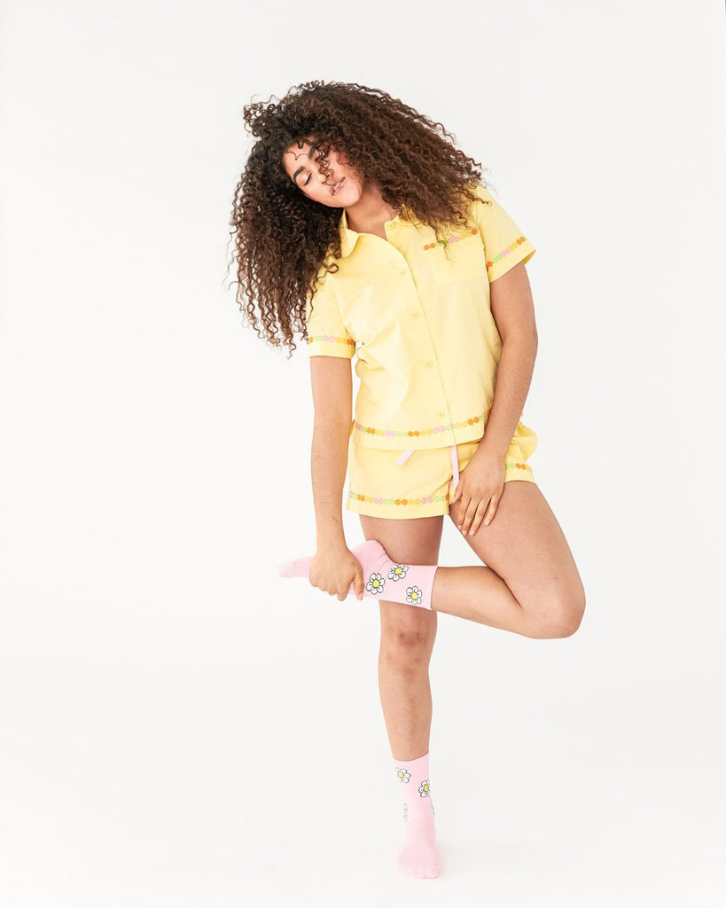 model wearing light yellow leisure shorts with a daisy applique trim at the bottom paired with matching short sleeve leisure shirt