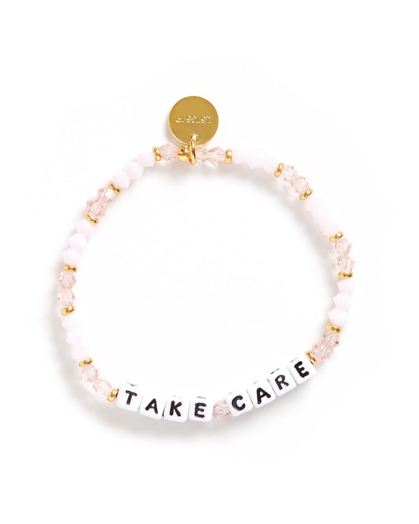 This bracelet features pink crystal beads, with white beads that spell 'Take Care'.