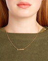 model shown wearing gold chain necklace with the word gratitude