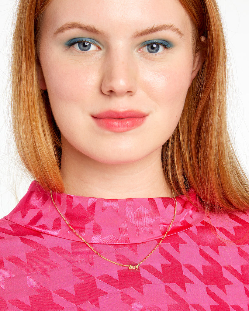 red headed model shown wearing gold chain necklace with the word joy