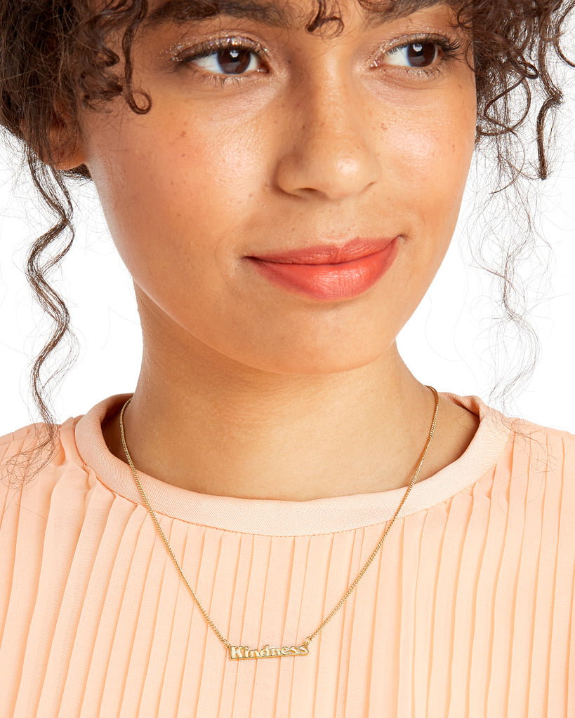 brunette model shown wearing gold chain necklace with the word kindness