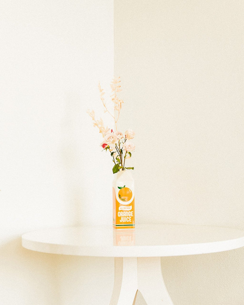 Orange juice carton-shaped porcelain vase shown holding flowers