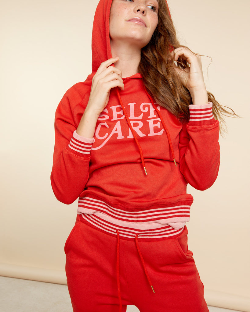 Soft red long sleeve pullover hoodie with Self Care graphic.