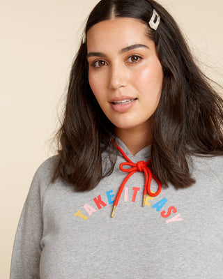 "Woman in grey long sleeve sweatshirt with rainbow striped hem, cuffs, and graphic ""take it easy"" in the center."